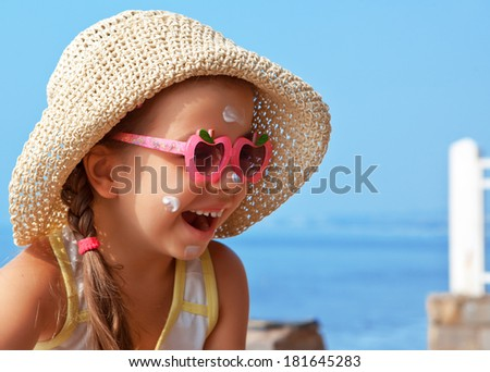 Happy child wearing sunscreen on my face against the sea