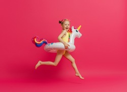 Happy child wearing swimsuit. Girl with swimming ring flamingo. Kid on a colored pink background.