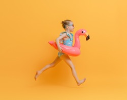 Happy child wearing swimsuit. Girl with swimming ring flamingo. Kid on a colored yellow background.