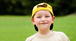 Happy child wearing yellow ball cap in outdoor portrait