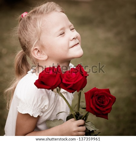 happy child with a bouquet of red roses