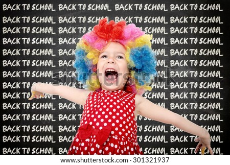 Happy child with back to school sign on chalkboard