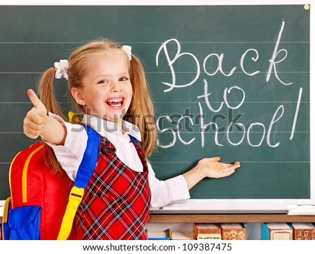 Happy child with backpack holding book. Isolated.