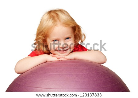 Happy child with ball playing sports. Adorable curly blond baby with blue eyes smiling with fitness ball. Space for your logo or symbol. Isolated on white background. Healthy lifestyle.