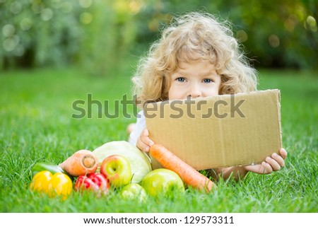 Happy child with fruits and vegetables lying on grass outdoors in spring park against green blurred background. Healthy eating concept. Paper blank with copyspace