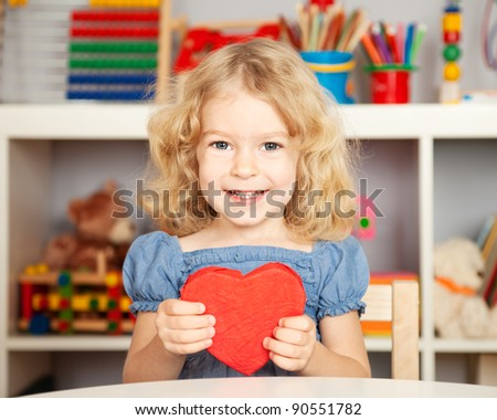 Happy child with handmade paper red heart in class. School concept