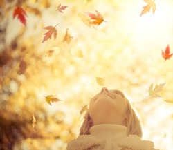 Happy child with maple leaves in autumn park against yellow blurred leaves background. Freedom concept
