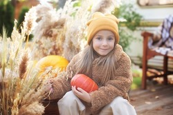 happy child with pumpkin outdoors in halloween. Smiling girl sit on porch with a pumpkin in her hands. Trick-or-treat. Happy little girl playing near home in fall garden. Child in cozy fall backyard.