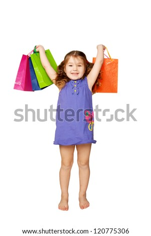 Happy child with shopping bags. She is enjoying the gifts and holidays. Isolated on white background