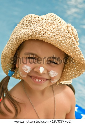 Happy child with sunscreen on my face against the background of water