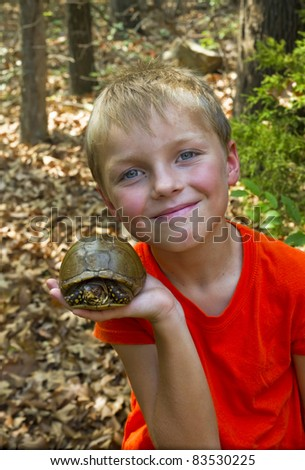 Happy child with tortoise in the woods - stock photo