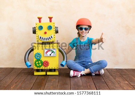 Happy child with toy robot. Funny kid playing at home. Success, creative and innovation technology concept Stock photo ©