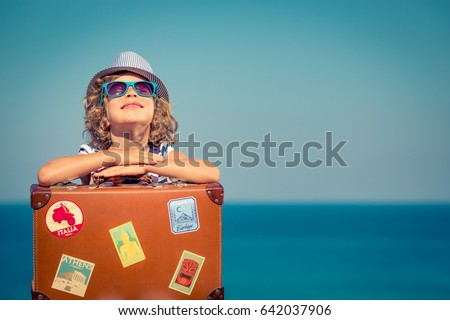 Happy child with vintage suitcase. Kid having fun on summer vacation. Travel and adventure concept #642037906