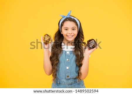 Happy childhood. Bakery confectionery concept. Kid girl hold glazed muffins. Delicious cupcakes. Adorable smiling child with cupcakes on yellow background. Treat someone with sweets. Yummy cupcakes.