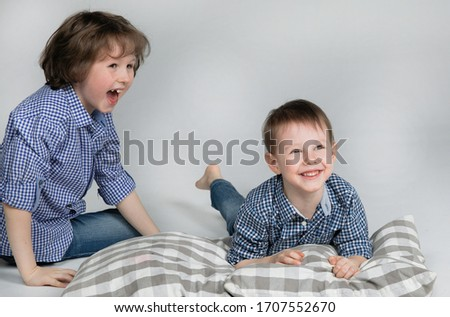 Happy childhood. Entertainment for children during home quarantine. Cronovirus World Pandemic. Naughty and funny little brothers sit on the pillows and laugh while watching a cartoon on a laptop