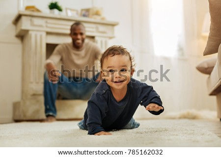 Happy childhood. Happy dark-haired afro-american man laughing and watching his cheerful young son crawling on the floor