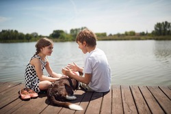Happy childhood in nature.Little children with dog sitting together on wooden near pond and talking.