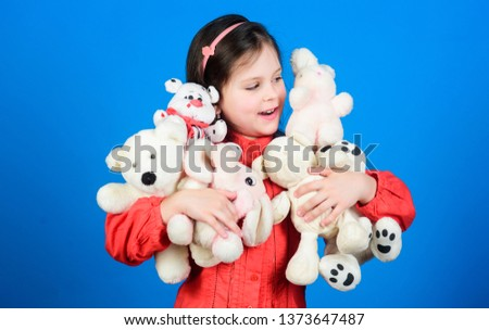 Happy childhood. Little girl play with soft toy teddy bear. Lot of toys in her hands. Childhood concept. Collecting toys hobby. Cherishing memories of childhood. Small girl smiling face with toys.