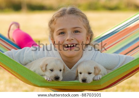 Happy childhood - little girl with cute puppies in hammock