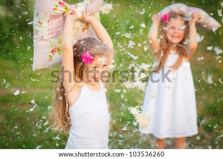 Happy childhood:little girls having fun with pillows outdoor