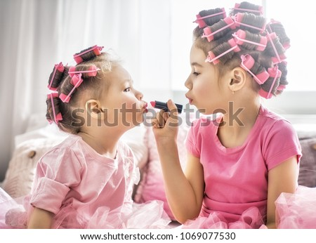 Happy childhood. Two sisters are doing hair and having fun. Children doing makeup sitting on the bed in the bedroom.