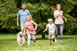 Happy children and parents with dog as family running in the nature
