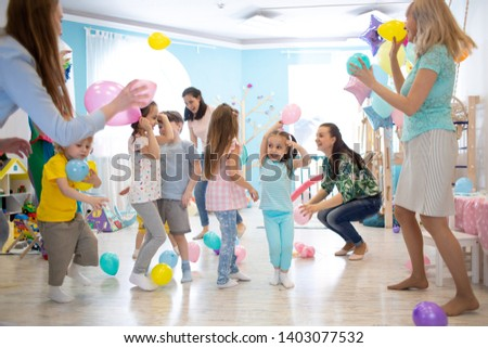 Happy children and their parents entertain and have fun with color balloon on kids birthday party