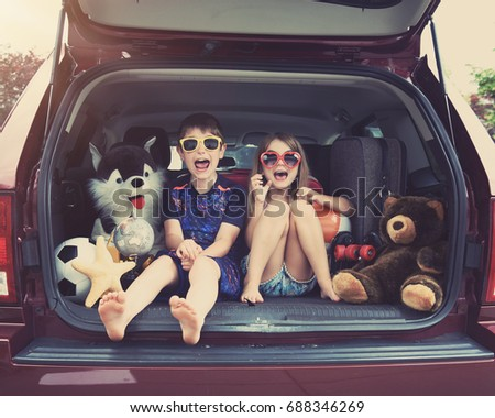Happy Children are sitting in the back of a car with travel objects waiting to go on a vacation. Use it for a family holiday lifestyle concept. #688346269