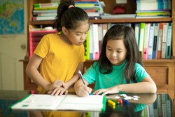 Happy children doing homework.Primary students having lesson together.Cheerful Asian pupils.Homeschooling.Kid writing on workbook.Map and shelves at background.Files and crayons.