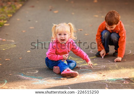 happy children draw with crayons on the pavement in the park