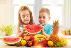 Happy children eating watermelon with fruits in kitchen, kids healthy eating concept