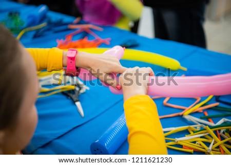 Happy children girl's hands with balloon on twisting art workshop #1211621230