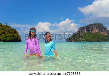 Happy children having fun in sea near tropical island, kids on beach vacation