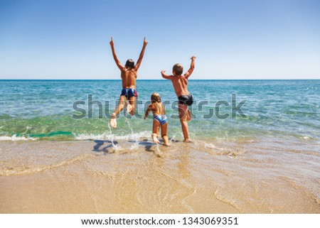 Happy children having fun on a beach running and jumping to the sea enjoying summer vacation #1343069351