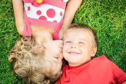 Happy children having fun outdoors. Kids playing in spring park. Boy and girl lying on green grass