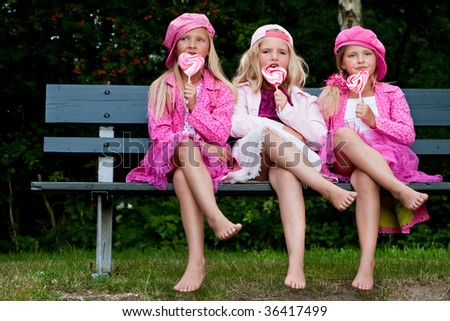 Happy children having pink clothes and a lollipop