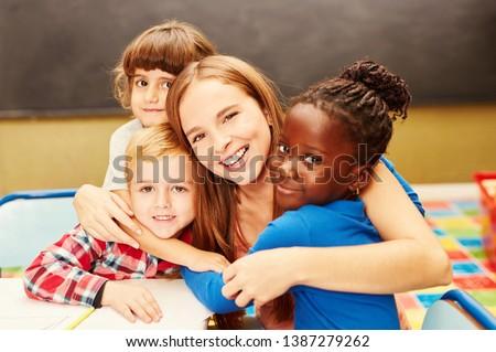 Happy children hug their childminder in child care