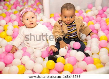 Happy children in colored ball on birthday on playground. The concept of childhood and holiday