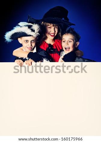 Happy children in halloween costumes posing over dark background. Copy space.