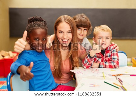 Happy children in multicultural kindergarten keep their thumbs up