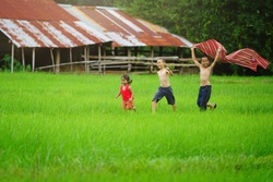 Happy children In the back of the house,Kids  playing on field,countryside of thailand.