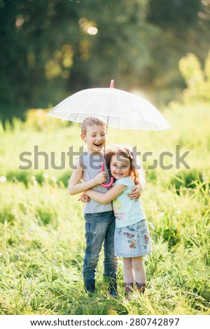 Happy children in the rain, shallow depth of field,  Funny kids playing outdoors in spring park. Brother and sister playing in the rain in summer, focus on children or raindrops