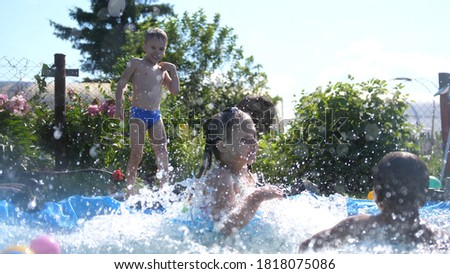 Photo of  Happy children jumping in outside swimming pool