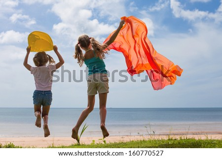 Happy children jumping on the beach on the day time