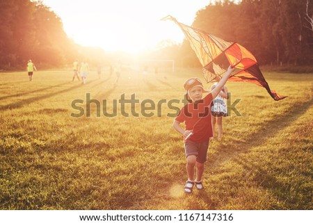 Happy children launch a kite in the field at sunset. Little boy and girl on summer vacation. #1167147316