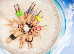 Happy children laying in a circle on the beach