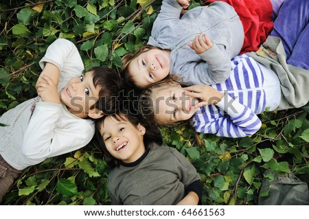 Happy children laying together in circle on ground