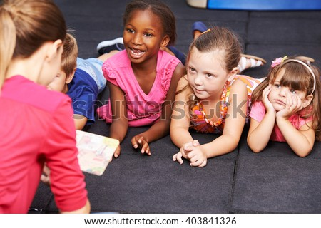 Happy children listening to fairytale book in preschool read by nursery teacher