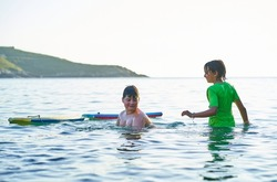 Happy children looking at camera playing in the sea with bodyboard. Children having fun outdoors. Concept of summer vacation and healthy lifestyle. Focus selective.