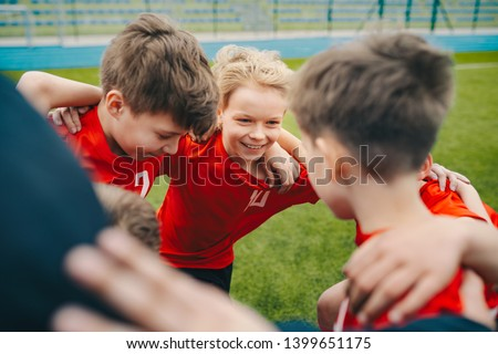 Happy children making sport. Group of happy boys making sports huddle. Smiling kids standing together with coach on grass sports field. Boys talking with coach before the football game